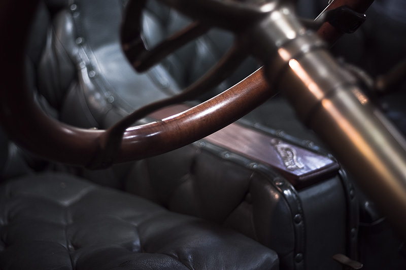 A copper & brass steering wheel in an antique car.