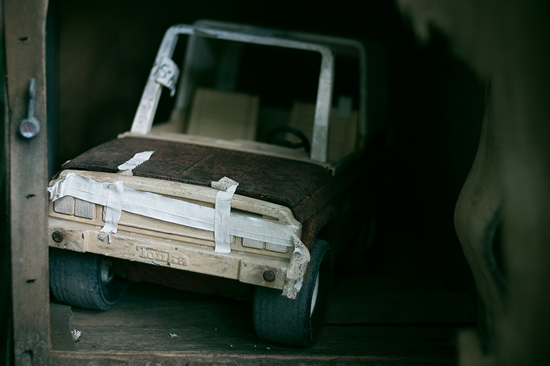A handmade toy car made of cardboard, inside a cupboard.