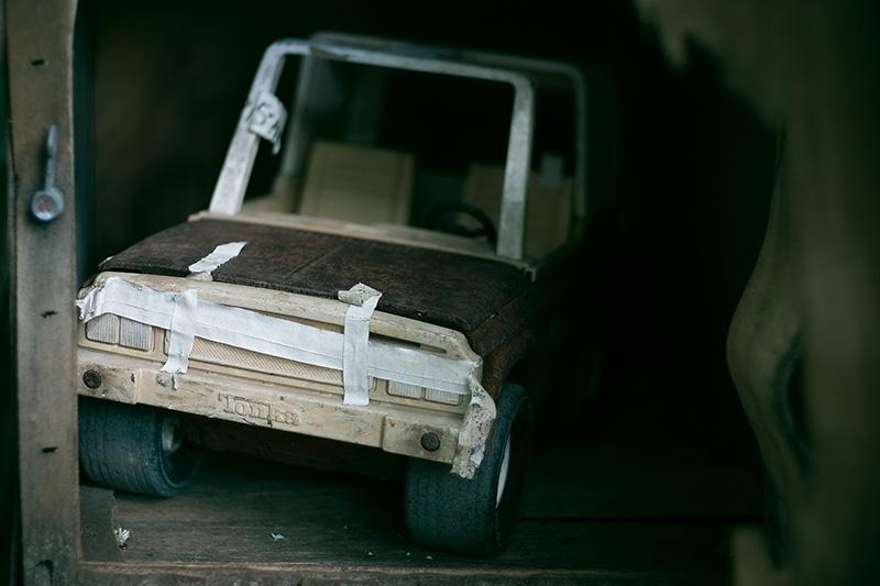 A handmade toy car made of cardboard, inside a cupboard.