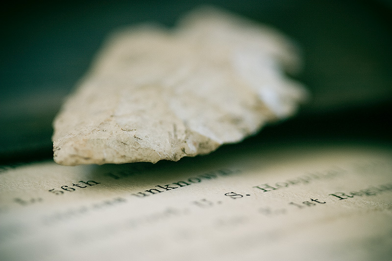 An arrowhead above a diagonal page of printed text.