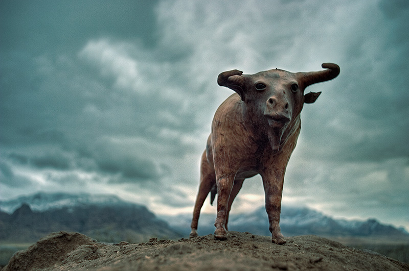 A leather sculpture of a bull-like animal stands against a backdrop of mountains and storm clouds.
