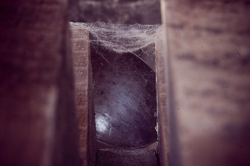 A cobweb-covered corridor with a partially-obscured metallic object at the end.