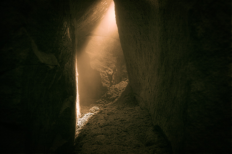 Light coming from a gap in the rock inside a cavern corridor.