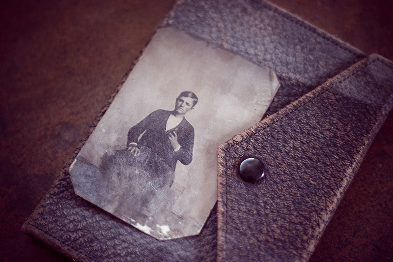 An antique tintype of a boy, sitting atop a closed leather photo album.