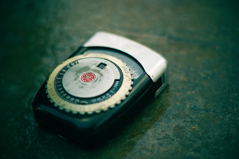 An old photographic light meter sitting on a wet cement surface.