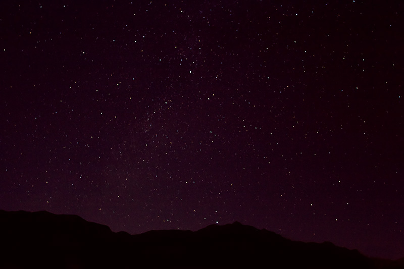 The night sky above silhouetted mountains.