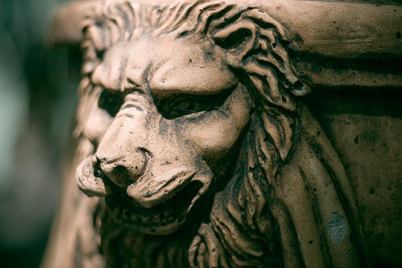 An ornamental lion on the side of a large pot.