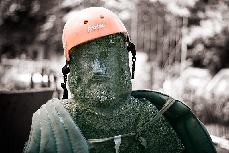A statue of Jesus, wearing a skateboard helmet and a life jacket.