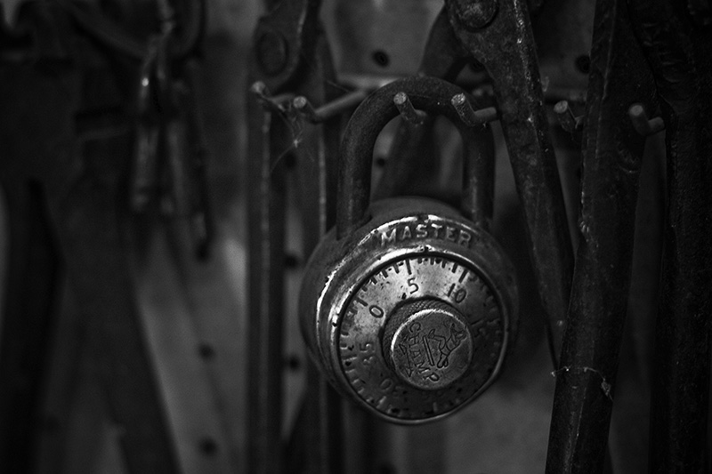 An antique Master lock hanging among numerous antique tools.