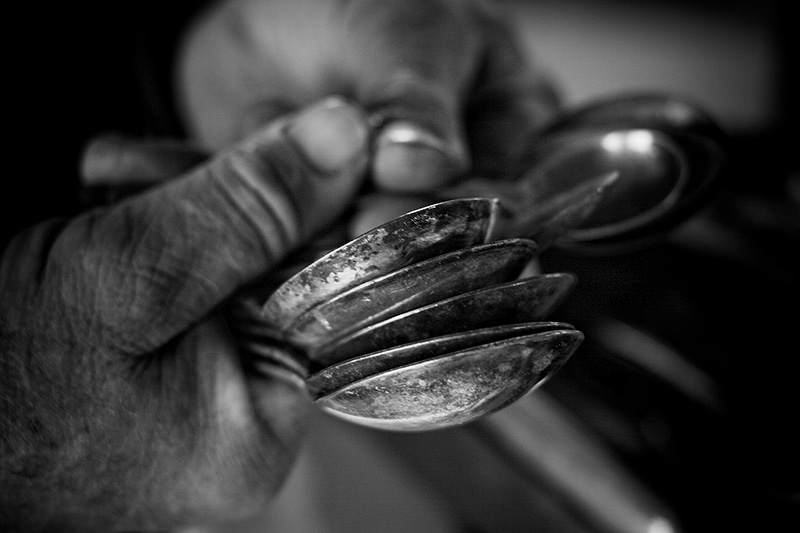 Two hands holding numerous old spoons.