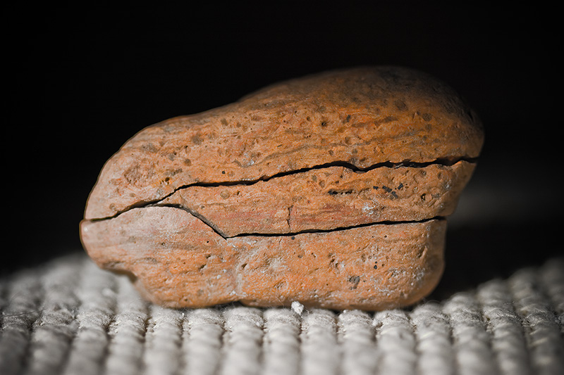 An orange rock cracked into three sections.