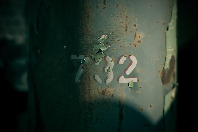 The numbers '702' painted in white onto a green cylinder.