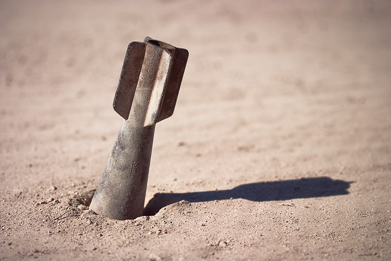 A cast-iron dummy bomb sticking out of the ground.