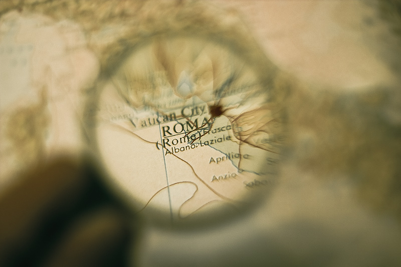 A magnifying glass showing Rome, Italy on a map.