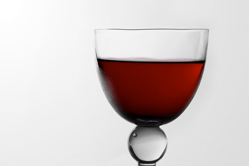 A glass with cranberry juice.