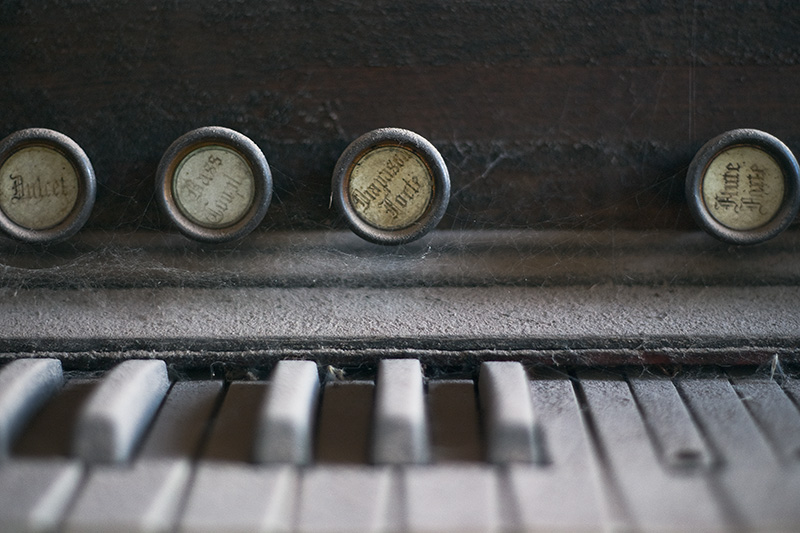 A detailed view of the keys and stops of a dust-covered antique organ.