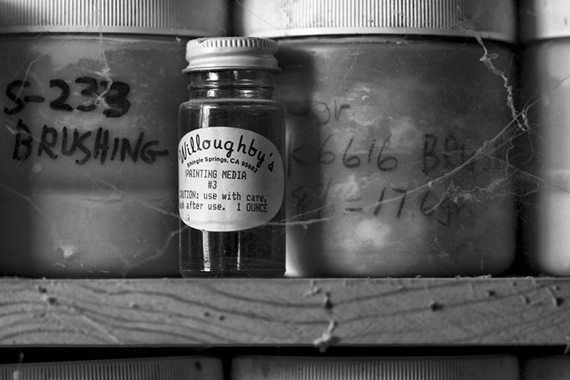 A small glass jar on a shelf, surrounded by larger containers.