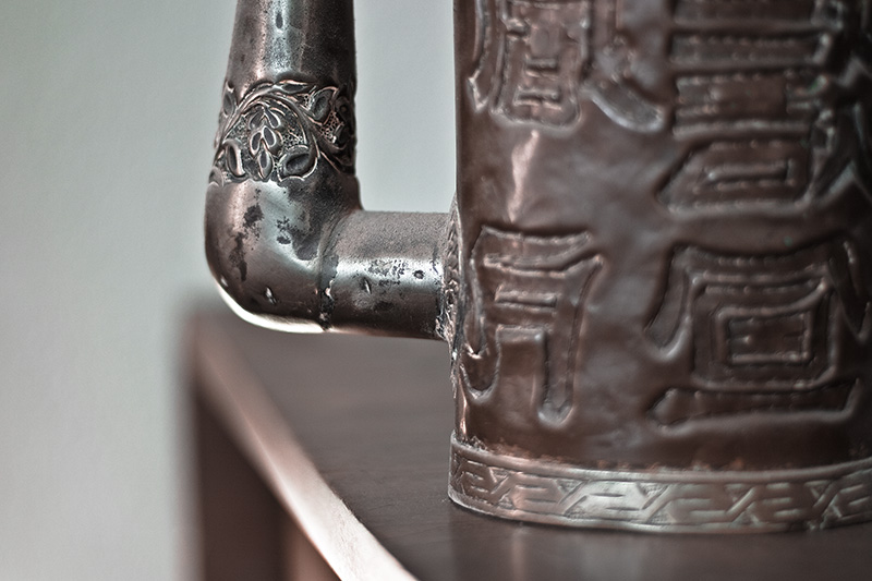 A decorative band around the spout of a copper pitcher.