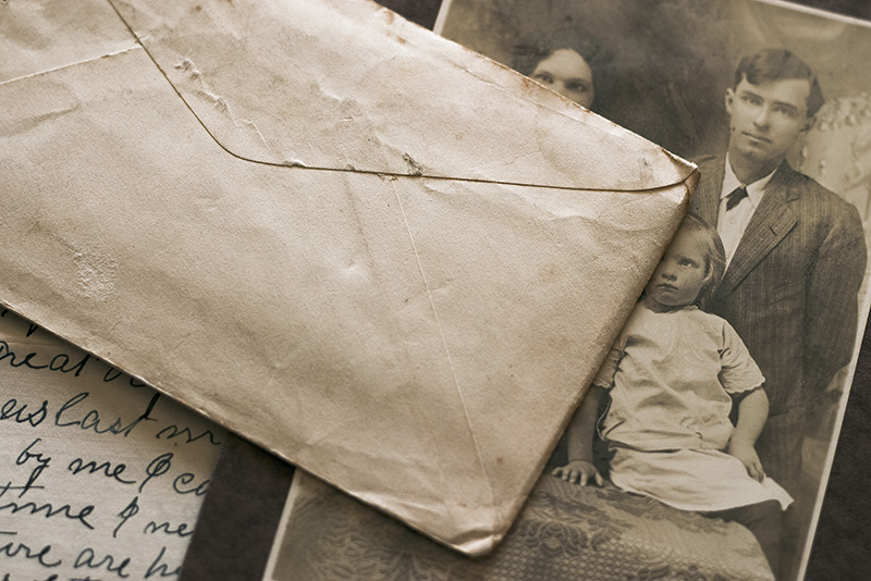 An unopened envelope sitting atop a family portrait and a letter.