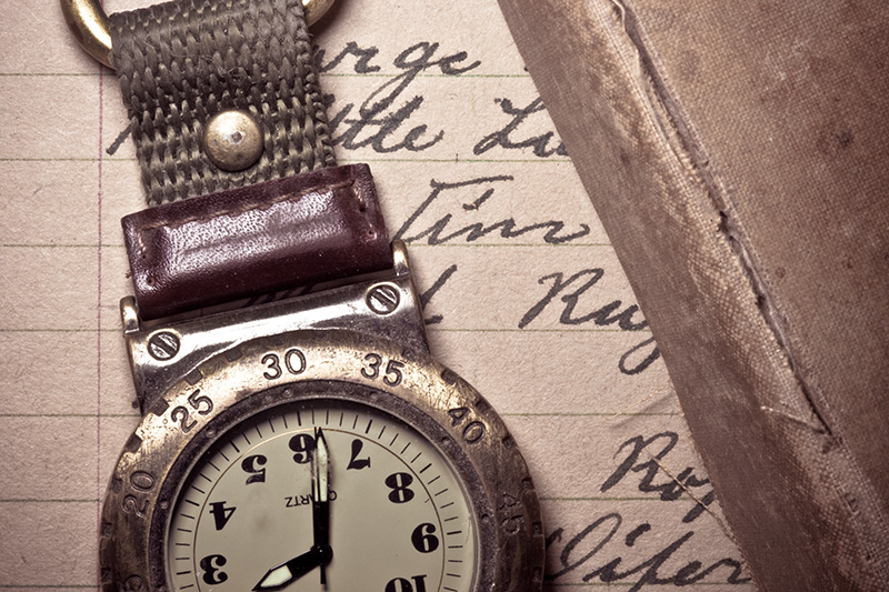 A well-worn pocket watch and book lying atop a handwritten letter.