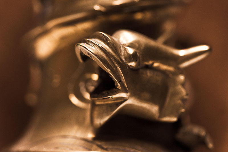 A brass dragon with its mouth open.