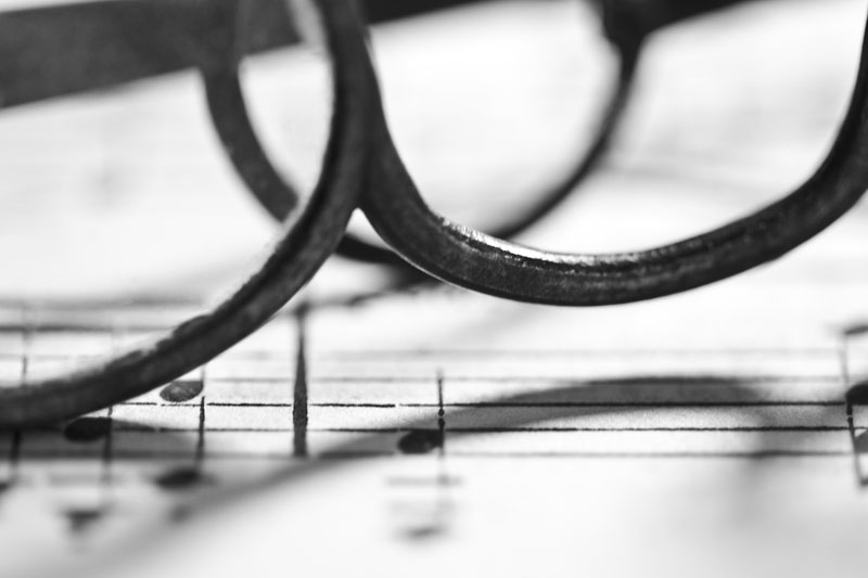 A pair of antique glasses on a sheet of music.