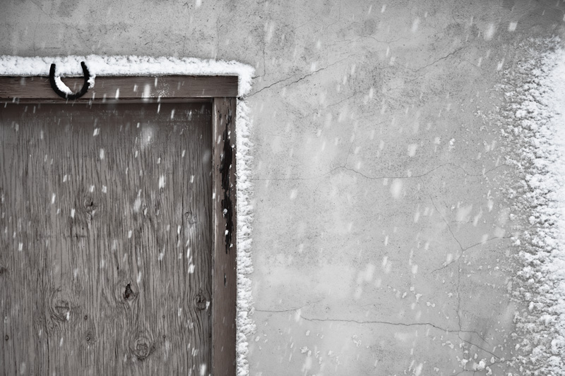 Snowfall built up around a door of a building.