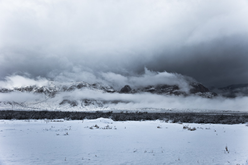 Snow covering the ground and mountains, with dark clouds menacing the sky.