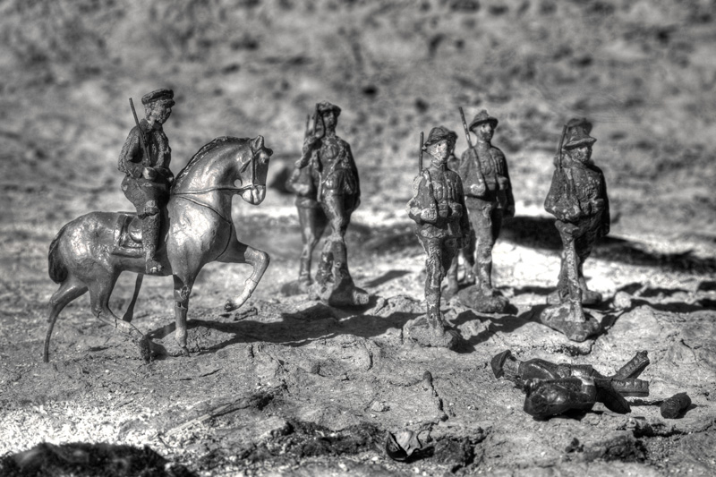 Soldiers on a burned-out battlefield march past dead bodies.
