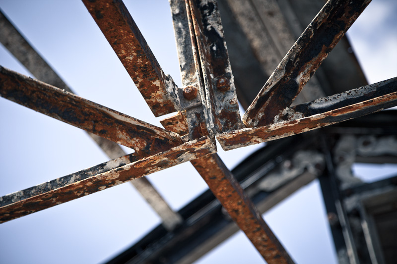 The rusted and burnt structure of an old building atop a peak.