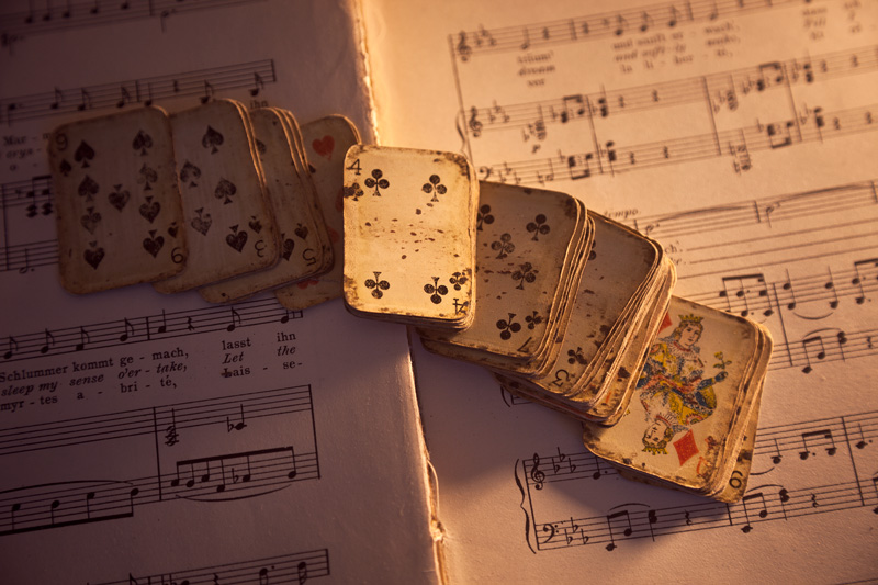 A miniature deck of cards atop sheet music.
