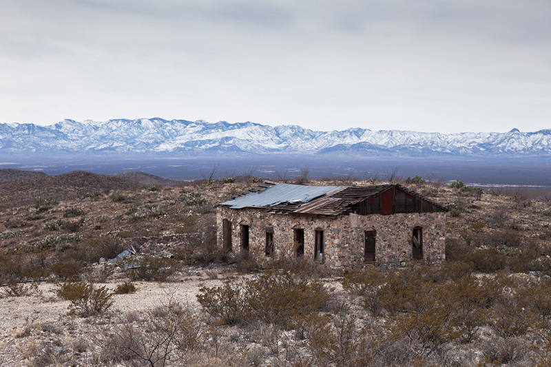 An abandoned building at the Johnny Bull Mine, with the snow-covered Chiricahua Mountains behind.