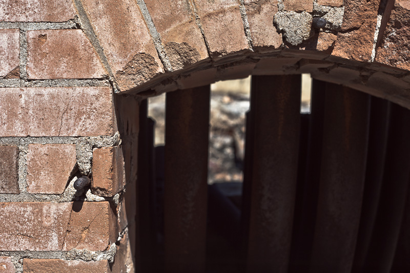 A small window through a brick building, with metal riser tubes behind.