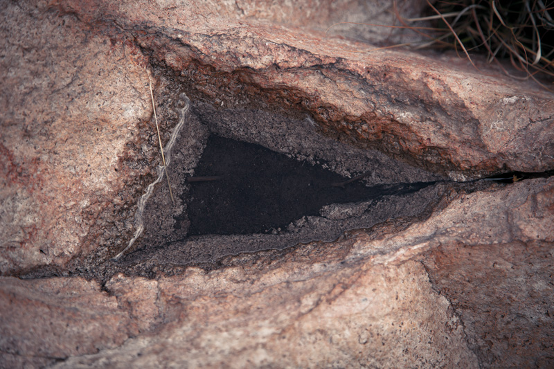 A triangle wedge in rock, filled with water.