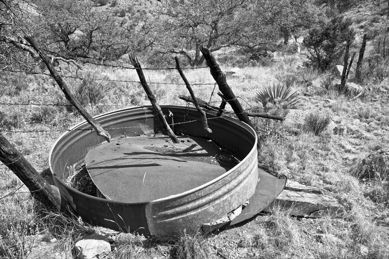 A gate in a fence and a broken horse & cattle watering tank along an old trail through a canyon in the Peloncillo Mountains.