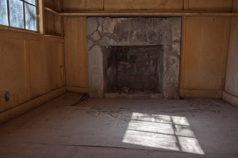 The interior of an abandoned structure with light entering through a window.