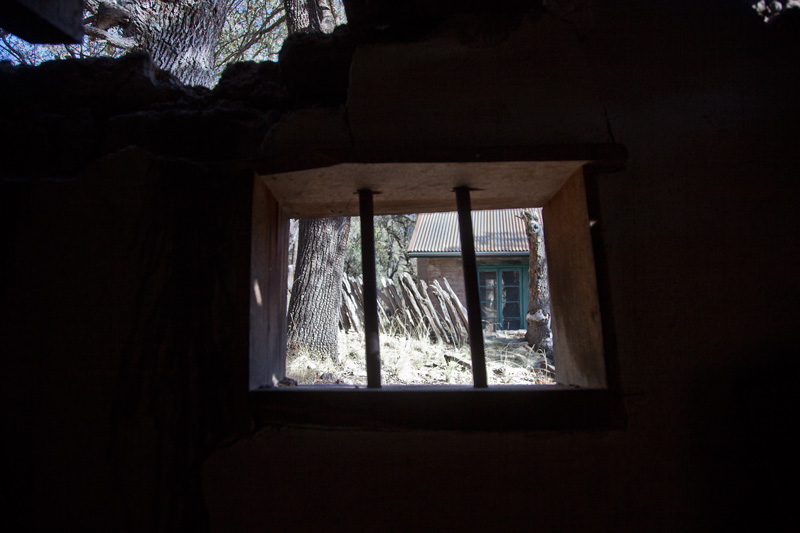 A view through the barred window of a partially collapsed structure.