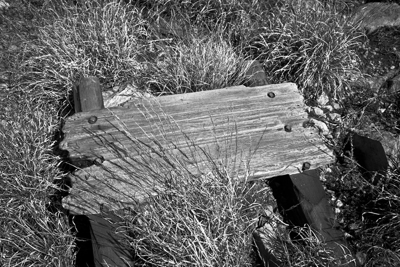 A fallen, worn wooden sign, no longer readable, atop Sentinel Peak in the Chiricahua Mountains.