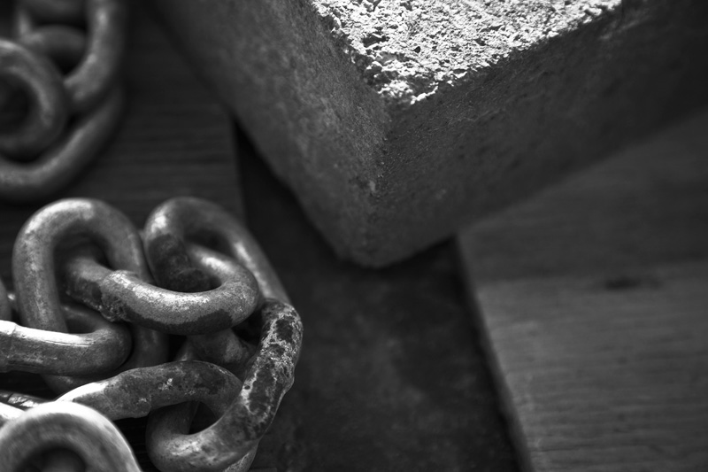 A chain and a brick atop wood.