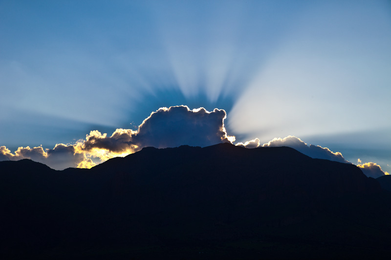 A burst of sunlight from behind a cloud, with a shadow cast by the cloud.