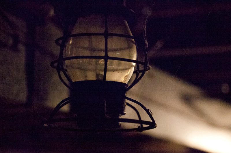 A lantern, barely illuminated itself.