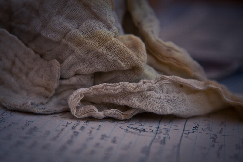 Cheesecloth atop a piece of paper with writing on it.