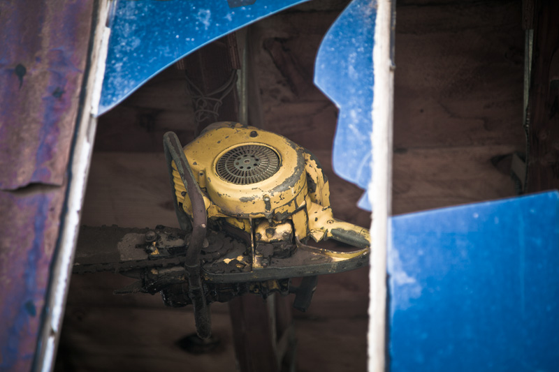 An antique chainsaw hangs from the rafters, viewed through a broken window.