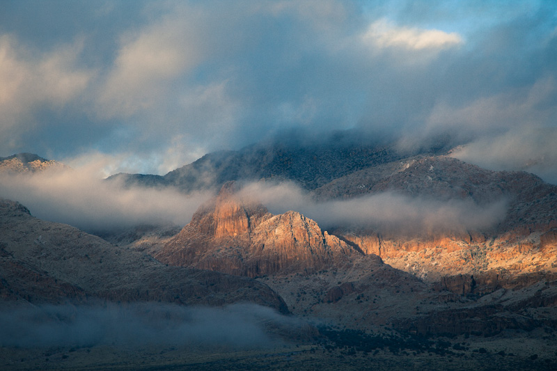 Sunlight coming through the clouds and striking Mangus Dome on the east slope of the Chiricahua Mountains.