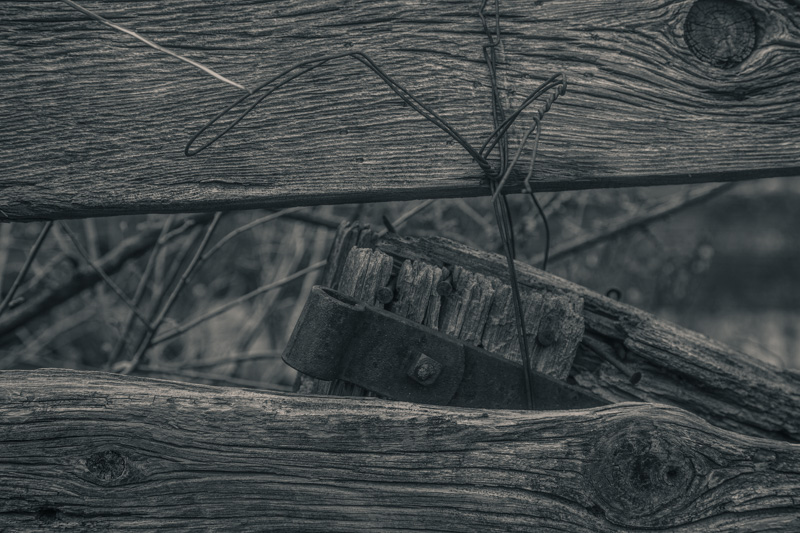 Old wooden fencing bound together by wire.